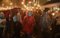 Foto: Spītējot lietum, vairāki tūkstoši cilvēku Rīgā dodas lāpu gājienā