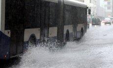Autobuss brauc pa pērkona negaisa laikā pārplūdušo Brīvības ielu.