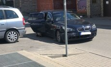 Foto: BMW Rīgā taranē ceļa zīmi un stāvošus auto