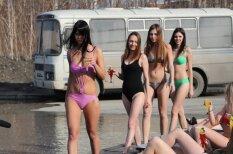 Sibīrijā meitenes sauļojas ielas malā un plunčājas dubļu peļķē