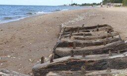 Aculieciniece fotogrāfijās iemūžina Daugavgrīvas pludmalē izskaloto kuģa vraku