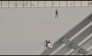 Video: Celtnieks ASV nokrīt no tilta un paliek karājoties trosē
