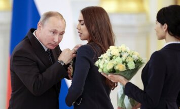 Russian President Vladimir Putin, left, listens to Russia s Margarita Mamun