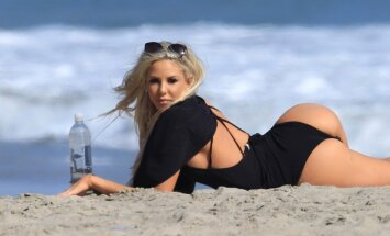 Īpaši lunkana 'Playboy' modele gozējas pludmalē