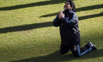 Argentina s soccer team coach Diego Maradona kneels while speaking to a journalist