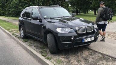 Foto: BMW vadītājs pie lielveikala auto novieto zālājā