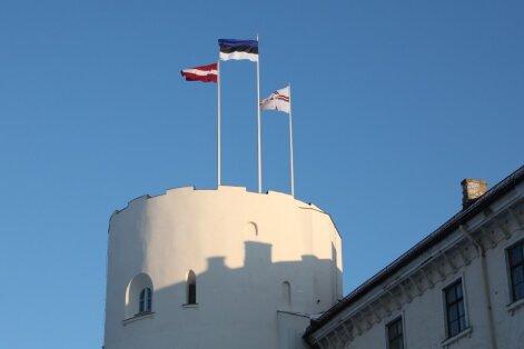 Foto: Rīgas pils Svētā Gara tornī Renārs Kaupers paceļ Igaunijas karogu