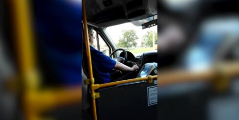Mikroautobusa šoferis pie stūres skatās filmas