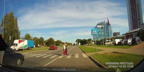 Bezkaunīgs riteņbraucējs izjož uz ceļa pie sarkanās luksofora gaismas
