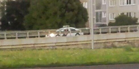 Policijas auto atpakaļgaitā cenšas uzbraukt uz viadukta
