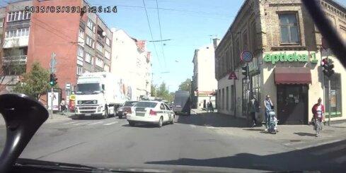Policijas auto aizbrauc pie sarkanās gaismas