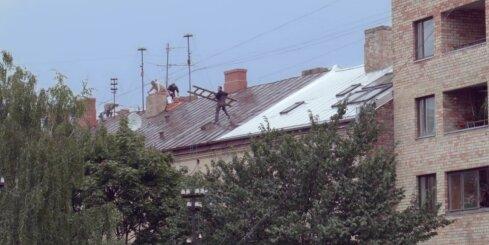 Rīgā pārgalvīgi celtnieki rosās pa slapjo ēkas jumtu un apdraud apkārtējos