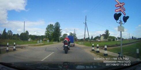 Motociklists apdzen uz dzelzceļa pārbrauktuves