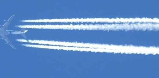 Foto: Lidmašīnu atstātās 'svītras' debesīs aizklāj mēnesi un sauli