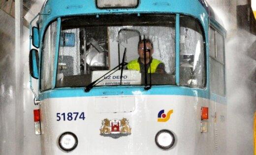 Bērni iesviež krāsu tramvaja priekšējā stiklā