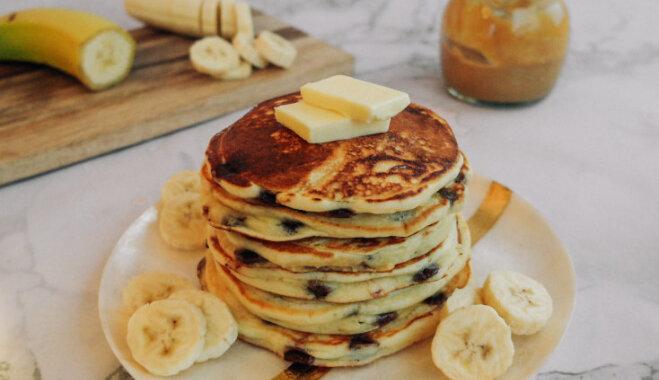 Классические блины с кусочками шоколада, поданные с бананом и кленовым сиропом