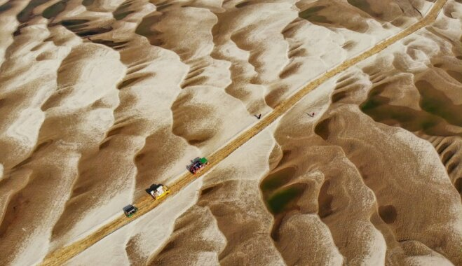 Dienas ceļojumu foto: Zemnieki šķērso nebeidzamas, tuksnesīgas kāpas Bangladešā