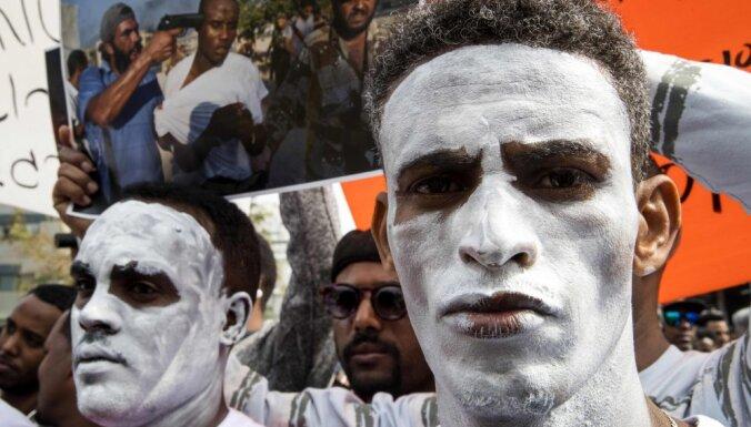 Āfrikas emigranti balti ķellētām sejām Izraēlā protestē pret izraidīšanu