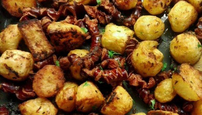 Cepeškrāsnī cepti kartupeļi pikantā marinādē ar kraukšķīgām mednieku desiņām