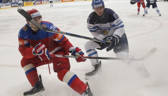 Alexei Yemelin of Russia in action with Aleksander Barkov of Finland