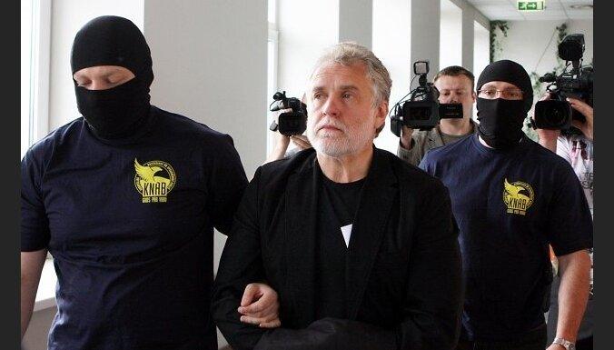 """Korupcijas novēršanas un apkarošanas biroja darbinieki konvojē uz Rīgas pilsētas Centra rajona tiesu saistībā ar iespējamām pretlikumīgām darbībām aizturēto AS """"Latvenergo"""" prezidentu Kārli Miķelsonu, lai lemtu par drošības līdzekļa piemērošanu."""