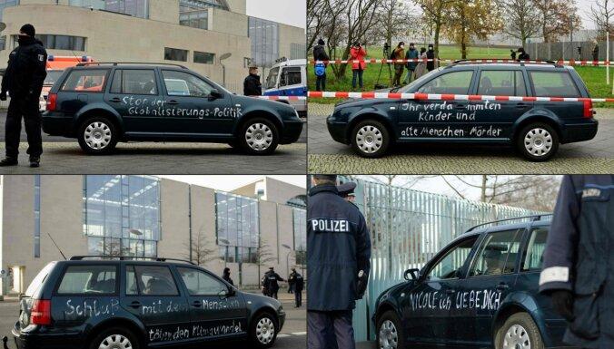 Merkeles biroja vārtos ietriekusies ar grafiti apzīmēta automašīna