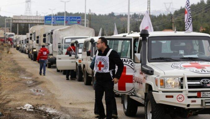 Foto: Badā mirstošu Sīrijas pilsētu sasniedz pirmās palīdzības kravas