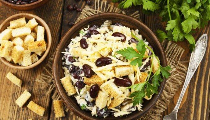 Sātīgie siera un pupiņu salāti ar ķiploku grauzdiņiem un marinētiem gurķiem