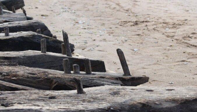 Daugavgrīvas pludmalē izskalotais senā kuģa vraka fragments nogādāts krastā