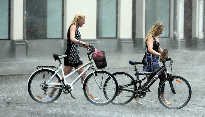 Jaunietes ar velosipēdiem pērkona negaisa laikā.
