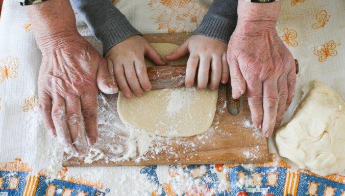 Vecmāmiņas un mazbērna rokas rullē mīklu
