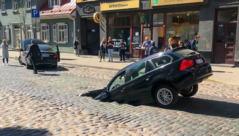 Foto: Ģertrūdes ielas bruģī ielūzis BMW; 'Rīgas siltums' uzņemas atbildību (plkst. 14)