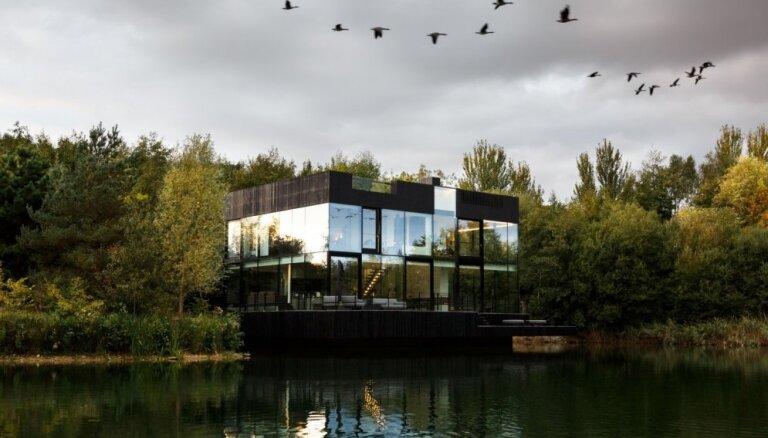 Foto: Pasakaina stikla māja uz ezera, kurā atspoguļojas apkārtnes ainava