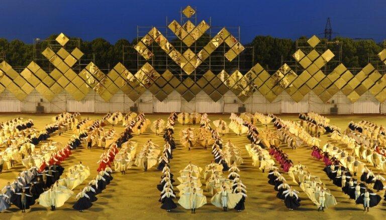 Ķīnā austi tautastērpi un olimpiskā vingrošana. Simtgades Deju svētki strīdu krustugunīs