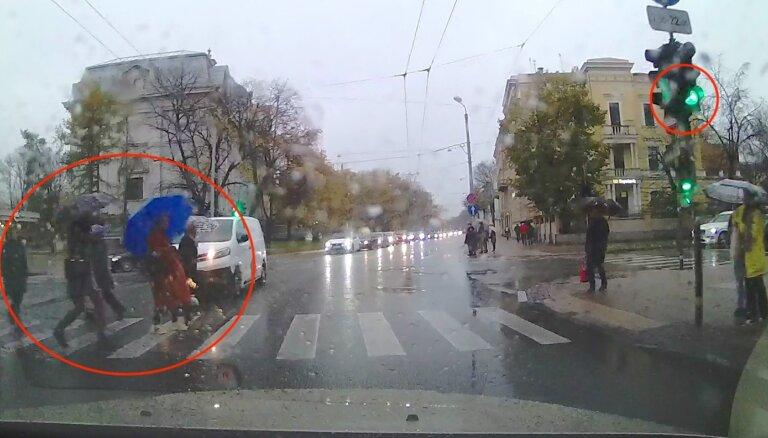 Video: Gājēju bara instinkts pie sarkanās gaismas – autovadītājs nobremzē pēdējā brīdī