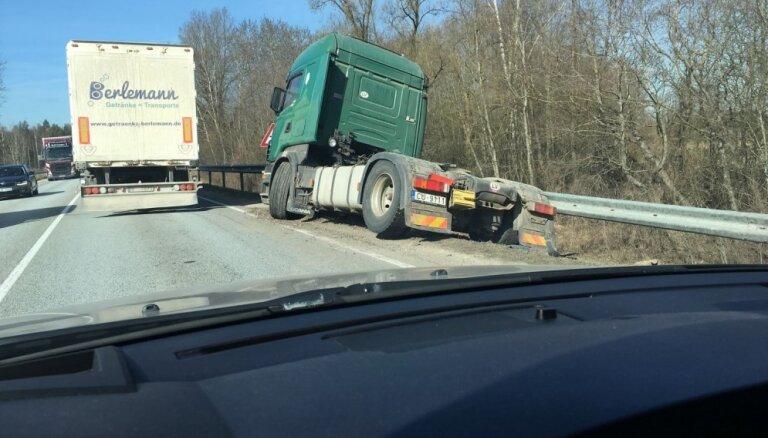Foto: Ķekavā kravas auto 'aizķeras' aiz aizsargbarjeras