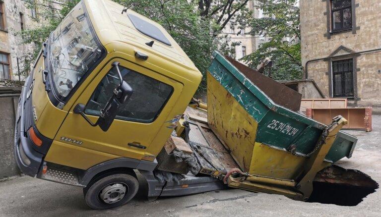 Foto: Rīgā iekšpagalma asfaltā ielūzis kravas automobilis