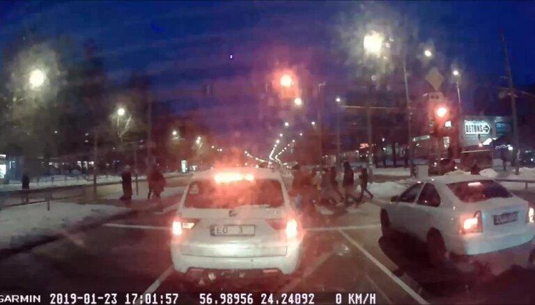 Video: Auto šķērso brauktuvi pie sarkanā luksofora signāla un biedē gājējus