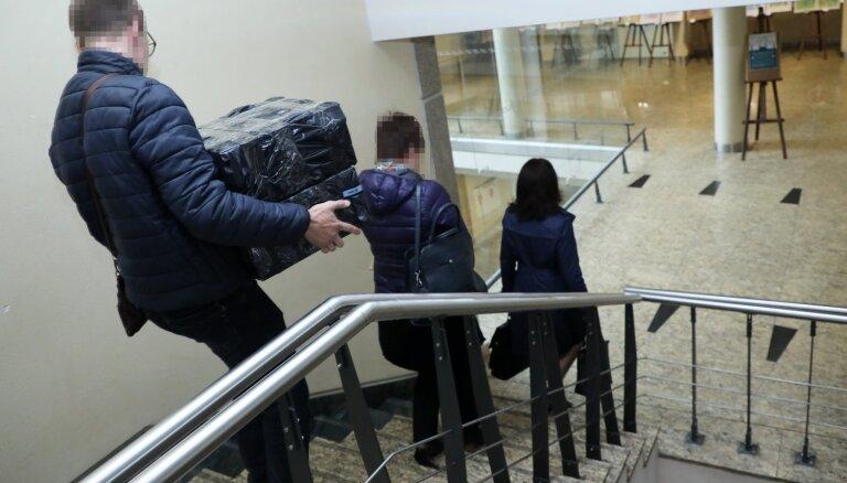 Foto: KNAB darbinieki pēc kratīšanas pamet Rīgas domi ar lieliem melniem saiņiem