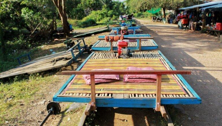 Bambusa platforma uz riteņiem: neparasts sliežu ceļš caur Kambodžas rīsu laukiem