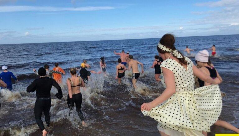 Foto: Simts cilvēku spirdzinošā marta dienā atklāj peldēšanas sezonu